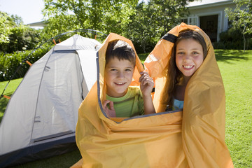 Brother and sister (8-10), wrapped in orange outer tent canvas, assembling dome tent on garden lawn, smiling, portrait