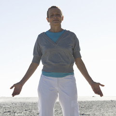 A mature woman meditating on a beach