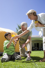 Boy (8-10) and grandfather assembling dome tent on garden lawn, grandmother serving orange juice, man tightening tent rope (surface level)