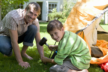 Father and son (8-10) assembling dome tent on garden lawn, boy hammering tent peg into grass with mallet, smiling, side view, portrait