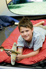 Boy (8-10) lying on red sleeping bag inside tent on garden lawn, holding toy aeroplane, smiling, portrait
