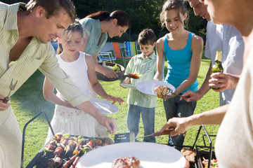 Three generation family standing beside barbecue grill in garden, adults serving children (8-13) food, smiling