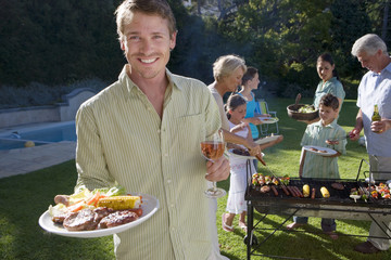 Three generation family standing beside barbecue grill in garden, focus on man holding plate of food in foreground, smiling, portrait