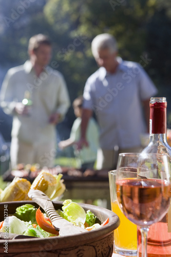 Two men talking in garden at family barbecue, focus on food and wine on table in foreground
