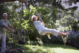 Senior woman swinging on garden rope swing, man pushing woman, smiling, side view, portrait