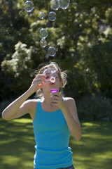 Girl (11-13), in turquoise vest, standing in summer garden, blowing soap bubbles into air with bubble wand, front view