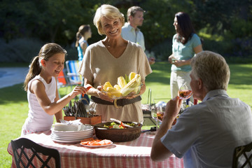 Three generation family having barbecue in summer garden, girl (8-10) standing beside grandmother at table, woman serving corn cobs, smiling