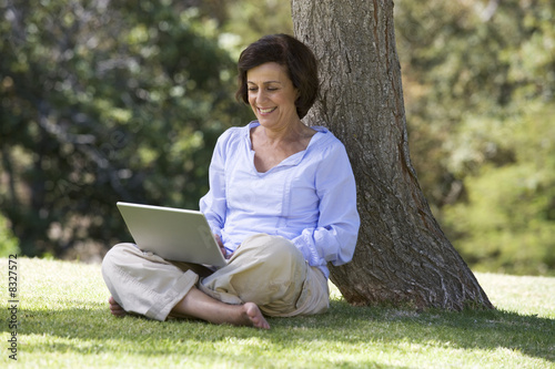 A senior woman sitting under a tree using a laptop