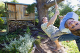 Father and son (8-10) swinging on garden rope swing near tree house, smiling, portrait (wide angle)