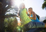 Two girls (8-13) swinging on garden rope swing, smiling, portrait, low angle view (lens flare)