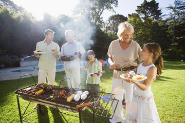 Family having barbecue in summer garden, senior woman serving granddaughter (8-10) beside grill, smiling (lens flare)