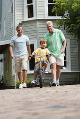 Boy (4-6) riding bicycle with stabilisers on pavement, father and grandfather looking on, smiling, front view, portrait (surface level)