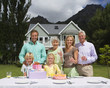 Three generation family celebrating birthday in summer garden in front of house, smiling, portrait