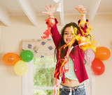 Excited girl (4-6) playing with streamers at birthday party, arms up, smiling, front view, portrait