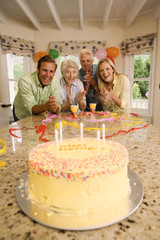 Parents and grandparents celebrating birthday at home, smiling, portrait, birthday cake on table in foreground