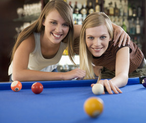 Two teenage girls playing pool