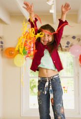 Excited girl (4-6) playing with streamers at birthday party, arms up, smiling, front view