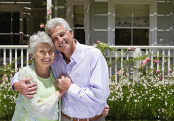 Senior couple standing in summer garden in front of house, arms around each other, holding hands, smiling, front view, portrait