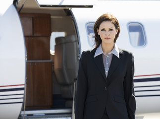 A business woman standing by a plane