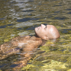 Young man swimming in a natural pool, close-up
