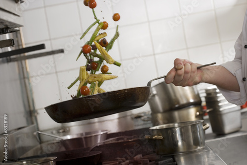 Male chef tossing stir fry vegetables in frying pan over gas hob in commercial kitchen, side view, mid-section (tilt)