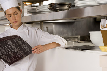 Female chef standing in commercial kitchen, looking at menu