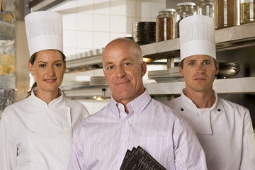 Restaurant manager standing with male and female chefs in commercial kitchen, smiling, front view, portrait