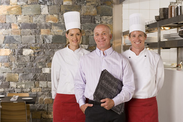 Restaurant manager standing with male and female chefs near commercial kitchen, smiling, front view, portrait