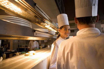 Male and female chefs standing at order counter in commercial kitchen, female chef smiling, portrait