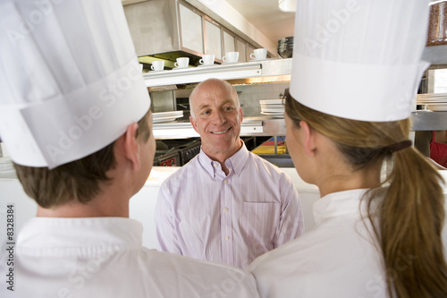 Restaurant manager talking to male and female chefs in commercial kitchen, smiling, view over shoulder