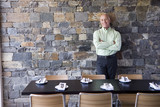Mature male restaurant owner standing beside table, leaning against stone wall, smiling, front view, portrait