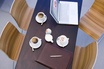 Laptop, menu and full coffee cups on café table, overhead view (still life)