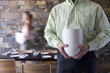 Waiter and waitress laying tables in restaurant, focus on man carrying stack of bowls in foreground (blurred motion)