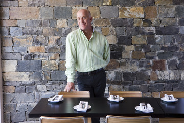 Mature male restaurant owner standing beside table, smiling, portrait