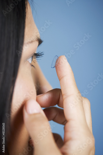 A young woman inserting a contact lens