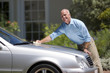 Senior man polishing silver car parked on driveway in front of house, smiling, side view, portrait