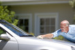 Senior man polishing silver car parked on driveway in front of house, smiling, side view