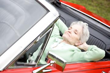 A senior woman sitting in a sports car