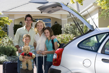Family standing with luggage beside open boot of parked car on driveway, boy (8-10) holding teddy bear, smiling, portrait