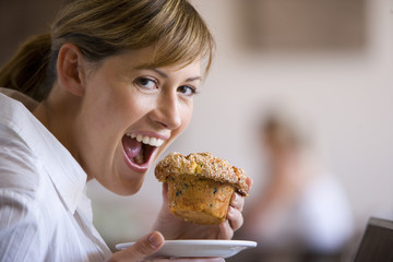 Woman eating muffin in café, smiling, close-up, side view, portrait (differential focus)