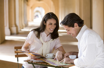 Couple sitting at pavement café table near colonnade, looking at tourist guide and street map, smiling