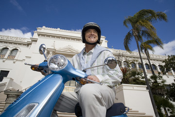 USA, California, San Diego, Balboa Park, senior man riding on blue motor scooter, smiling, side view, low angle view