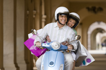 Senior couple riding on motor scooter near colonnade, woman holding shopping bags, smiling, front view