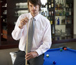 A businessman playing pool in a bar