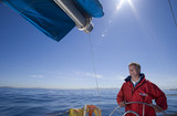 Man in red jacket standing at helm of sailing boat out at sea, smiling, steering (lens flare)