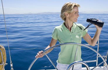 Woman in green polo shirt standing at helm of sailing boat out at sea, steering, looking through binoculars, smiling