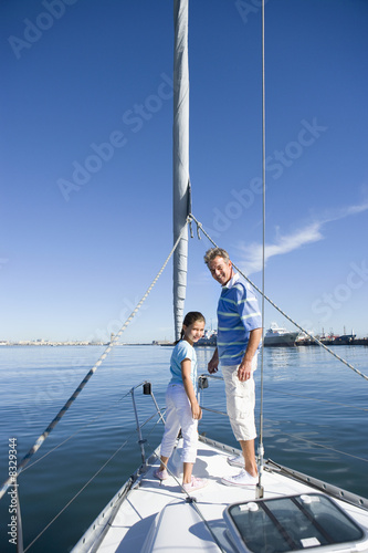 Father and daughter (8-10) standing at bow of sailing boat, smiling, side view, portrait