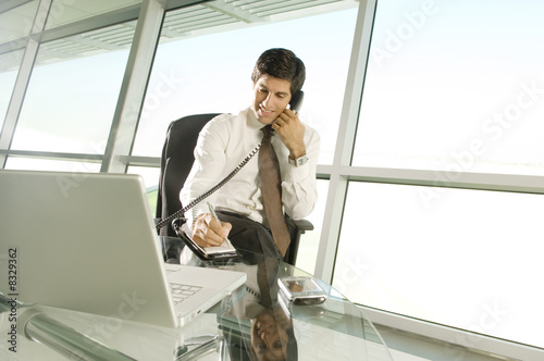 A businessman sitting at his desk talking on the telephone