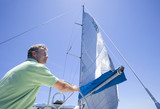 Man in green polo shirt standing at helm of sailing boat, steering, rear view, low angle view