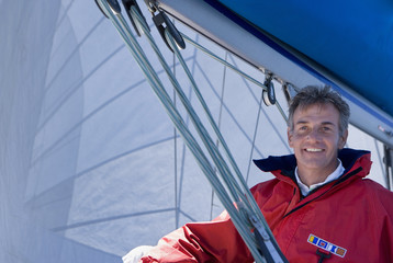 Man in red jacket sitting on deck of sailing boat below sail, smiling, portrait, low angle view